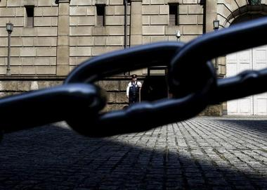 File picture of a security officer seen through a chain link as he stands...