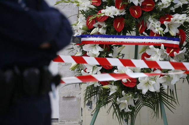 A wreath of flowers is displayed in front of the church a day after a hostage-taking in Saint-Etienne-du-Rouvray near Rouen in Normandy, France, where French priest, Father Jacques Hamel, was killed with a knife and another hostage seriously wounded in an attack on the church that was carried out by assailants linked to Islamic State, July 27, 2016.    REUTERS/Pascal Rossignol