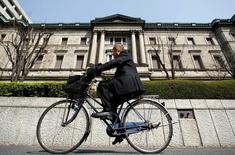 El Banco de Japón expandió el viernes su estímulo monetario al duplicar las compras de fondos cotizados en bolsa (ETFs), con lo que cedió a la presión del Gobierno y los mercados financieros pero decepcionó a los inversores que esperaban medidas aún más audaces. En la imagen de archivo, un hombre pasa en bicicleta ante el edificio del Banco de Japón en Tokio, el 18 de marzo de 2009. REUTERS/Yuriko Nakao