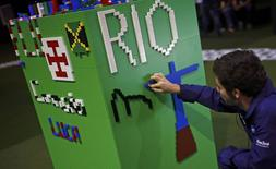 A man arranges LEGO bricks to build a Rio sign during a LEGO presentation of a massive model of the city including the Olympic sites at the Media Center in Rio de Janeiro, Brazil August 1, 2016. REUTERS/Nacho Doce