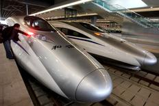 A man looks at the bullet trains serving the new high-speed railway linking Shanghai and Hangzhou in Shanghai October 26, 2010. REUTERS/Aly Song