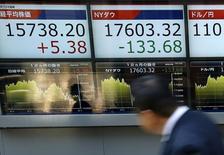 Un hombre camina frente a una pantalla que muestra información bursátil, afuera de una correduría en Tokio, Japón. 6 de abril de 2016. Las acciones globales caían por tercera sesión seguida el miércoles, deprimidas por el creciente nerviosismo en torno a las políticas de los bancos centrales y a la subida de los rendimientos de los bonos globales, pese al repunte de las acciones bancarias de Europa. REUTERS/Issei Kato