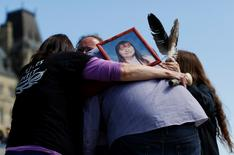 "A photograph of Terrie Ann Dauphinais is seen as participants hug after singing a song during the ""24 Hour Sacred Gathering of Drums"" protest calling for an inquiry into missing and murdered aboriginal women, on Parliament Hill in Ottawa May 12, 2014. Dauphinais was found murdered in her Calgary home on April 29, 2002 and the case remains unsolved. REUTERS/Chris Wattie"