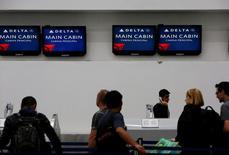 Pasajeros revisan sus vuelos en el mesón de Delta Air Lines en Ciudad de México. 8 de agosto de 2016. Delta Air Lines Inc dijo que cancelará casi 250 vuelos el martes, en un intento por restaurar sus operaciones tras un apagón que afectó a sus sistemas computacionales el lunes, lo que provocó la cancelación de cerca de 1.000 vuelos. REUTERS/Ginnette Riquelme