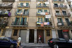 Banners against touristic apartments hang from balconies as people walk past them at Barceloneta neighborhood in Barcelona, Spain, August 18, 2015. REUTERS/Albert Gea/File Photo