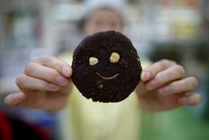 A sales assistant poses for photographs with a mealworm cookie in Seoul, South Korea, August 8, 2016. Picture taken August 8, 2016.  REUTERS/Kim Hong-Ji