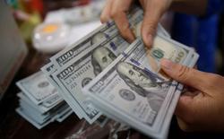 Служащий банка в Ханое пересчитывает доллары США. Доллар подешевел в пятницу после того, как данные неожиданно указали на то, что розничные продажи в США не изменились в июле, в то время как цены производителей снизились, спровоцировав опасения о росте экономики в третьем квартале.  REUTERS/Kham