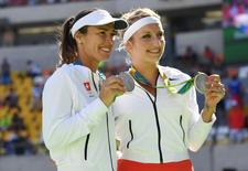 Aug 14, 2016; Rio de Janeiro, Brazil; Martina Hingis (SUI) and Timea Bacsinszky (SUI) show off their medals in a women's doubles tennis medal ceremony against  at Olympic Tennis Centre during the Rio 2016 Summer Olympic Games. Mandatory Credit: Kyle Terada-USA TODAY Sports