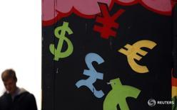 Символы различных валют на стене в Дублине 22 октября 2014 года. Доллар занял оборонительную позицию на торгах понедельника, испытывая давление со стороны пессимистичных данных из США, которые умерили ожидания инвесторов в отношении скорого подъема ставок ФРС. REUTERS/Cathal McNaughton