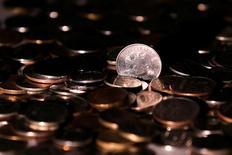 Рублевые монеты. Рубль начал биржевые торги понедельника ростом на фоне сохранения позитивной динамики нефти, достигшей трехнедельных максимумов; на стороне российской валюты начинающийся сегодня налоговый период и также высокие рублевые процентные ставки, привлекательные для спекуляций carry-trade. REUTERS/Maxim Zmeyev/Illustration