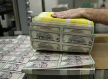 Billetes de 5 dólares en la Casa de la Moneda de Estados Unidos en Washington, mar 26, 2015. La rentabilidad de la deuda de empresas de mercados emergentes ha provocado una fiebre compradora que ha llevado los rendimientos a mínimos de 13 meses y que eleva el riesgo de que algún problema externo, posiblemente en Estados Unidos o China, provoque una huida desordenada.   REUTERS/Gary Cameron