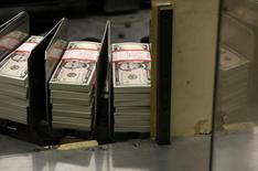 Fajos con billetes de cinco dólares en la Casa de la Moneda de Estados Unidos, mar 26, 2015. El dólar bajó el lunes frente a una cesta de destacadas monedas, presionado por débiles datos económicos en Estados Unidos que moderaron las expectativas respecto a un alza de las tasas de interés de la Reserva Federal durante este año.  REUTERS/Gary Cameron