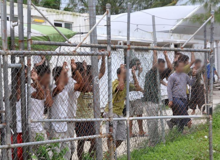 Asylum-seekers look through a fence at the Manus Island detention centre in Papua New Guinea March 21, 2014.  AAP/Eoin Blackwell/via REUTERS/Files