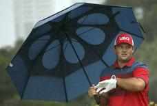 2016 Rio Olympics - Golf - Preliminary - Men's Individual Stroke Play - Olympic Golf Course - Rio de Janeiro, Brazil - 12/08/2016.  Patrick Reed (USA) of the United States walks off the tee under an umbrella during the second round of the men's Olympic golf competition. REUTERS/Andrew Boyers