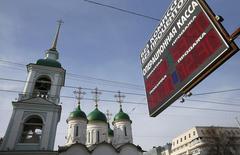 Табло с курсами валют около церкви в Москве 24 февраля 2015 года. Международное рейтинговое агентство Moody's пересмотрело в сторону повышения прогноз для крупнейших развивающихся рыночных экономик на 2016-17 годы, в том числе для Китая, Бразилии и России. REUTERS/Maxim Shemetov
