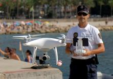 Local police officer Agustin Mirete controls a drone equipped with a camera used for surveillance tasks in the Poniente beach at the eastern costal town of Benidorm, Spain, August 18, 2016. REUTERS/Heino Kalis