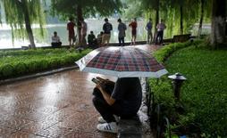 """Un grupo de personas juega a """"Pokemon Go"""" bajo la lluvia junto al lago Hoan Kiem en Hanoi, Vietnam. 18 ago 2016. Los aficionados asiáticos del juego de realidad aumentada Pokemon Go están en busca de mejores proveedores de servicios de telecomunicaciones y equipos tecnológicos para superar las dificultades que les genera la mala señal de los dispositivos móviles en su afán por cazar las populares criaturas virtuales. REUTERS/Kham"""