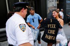 "A shopper shows her ""The Life of Pablo"" merchandise to NYPD officers after visiting a pop up store featuring fashion by Kanye West in Manhattan, New York, U.S., August 19, 2016. REUTERS/Eduardo Munoz"
