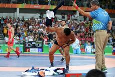 2016 Rio Olympics - Wrestling - Final - Men's Freestyle 65 kg Bronze - Carioca Arena 2 - Rio de Janeiro, Brazil - 21/08/2016. The coach of Mandakhnaran Ganzorig (MGL) of Mongolia takes off his clothes as he protests after the match against Ikhtiyor Navruzov (UZB) of Uzbekistan. REUTERS/Toru Hanai