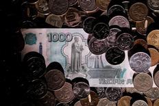 Рублевые монеты и купюра. Рубль подешевел на биржевой сессии понедельника вслед за снижением нефти после многодневного ралли, при этом в первой половине дня сдерживающим его ослабление фактором могла выступать продажа валютной выручки под предстоящие 25 и 29 августа выплаты экспортерами НДПИ и налога на прибыль. REUTERS/Maxim Zmeyev/Illustration