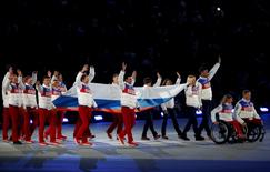 Performers carry the Russian national flag during the closing ceremony of the 2014 Paralympic Winter Games in Sochi, Russia, March 16, 2014. REUTERS/Alexander Demianchuk/File Photo