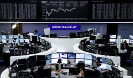 Traders work at their desks in front of the German share price index, DAX board, at the stock exchange in Frankfurt, Germany, August 23, 2016. REUTERS/Staff/Remote