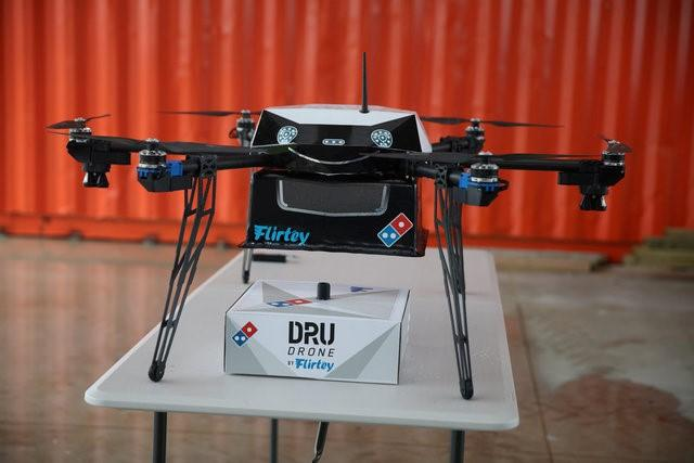A pizza delivery drone sits with a pizza box underneath before a test flight in Auckland, New Zealand, August 25, 2016.   Domino's/Handout via REUTERS