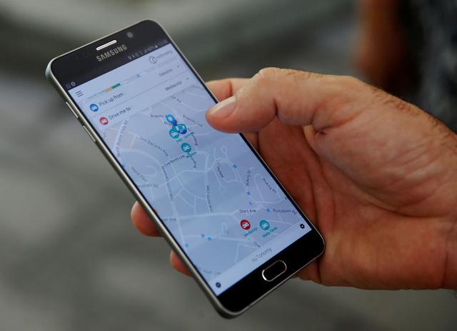 Um membro da equipe de nuTonomy demonstra a sua aplicação de táxi de reserva auto-dirigindo em uma unidades de telefones celulares durante o seu julgamento público em Singapura 25 de agosto de 2016. REUTERS / Edgar Su