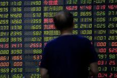 Un inversor mira un tablero electrónico que muestra información bursátil, en una correduría en Shanghái, China. 23 de junio de 2016. Las acciones chinas cayeron el jueves a su nivel más bajo en casi dos semanas debido a un retroceso de los papeles ligados a los bancos y las firmas inmobiliarias, luego de que el Gobierno impuso normas más estrictas a los préstamos para frenar los riesgos en el sistema financiero. REUTERS/Aly Song