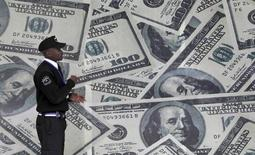 A security guard walks past a montage of U.S. $100 dollar bills outside a currency exchange bureau in Kenya's capital Nairobi, July 23, 2015.    REUTERS/Thomas Mukoya/File Photo - RTX2DSFL