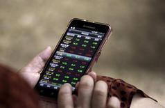 Инвестор в брокерской компании в Пекине проверяет фондовую информацию на своем смартфоне. Китайский фондовый рынок закрыл пятничные торги вблизи уровней предыдущей сессии, растеряв набранное ранее преимущество в связи с возобновившимся снижением акций сектора недвижимости. REUTERS/Jason Lee/File Photo