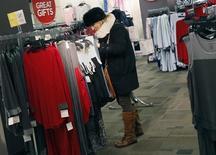 Una mujer comprando ropa en una tienda en Nueva York. 27 de noviembre de 2012. El crecimiento económico de Estados Unidos fue un poco más lento a lo previsto inicialmente en el segundo trimestre, debido a que las empresas redujeron agresivamente sus existencias de bienes no vendidos, contrarrestando un arranque en el gasto del consumidor. REUTERS/Shannon Stapleton