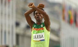 2016 Rio Olympics - Athletics - Final - Men's Marathon - Sambodromo - Rio de Janeiro, Brazil - 21/08/2016. Feyisa Lilesa (ETH) of Ethiopia celebrates.   REUTERS/Athit Perawongmetha