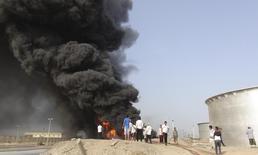 Люди у горящих нефтяных хранилищ на НПЗ в Адене, Йемен, 27 июня 2015 года. Нефть дорожает после ракетного удара Йемена по нефтяным объектам Саудовской Аравии. REUTERS/Stringer