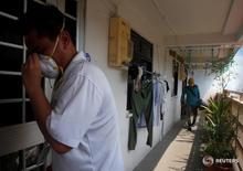 Сотрудник Национального управления по охране окружающей среды Сингапура (слева) в здании, находящемся близ места проживания заразившегося вирусом Зика человека 29 августа 2016 года. Сингапур подтвердил 41 случай заражения вирусом Зика на территории страны, главным образом, среди иностранных рабочих, и сообщил, что это число может вырасти.  REUTERS/Edgar Su