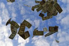 Долларовые банкноты. Фотография сделана под Севильей 16 ноября 2014 года. Банк России повысил оценку задолженности банков по своим операциям рефинансирования на конец 2016 года до 1,3 триллиона рублей в связи с пересмотром среднегодовой цены на нефть, говорится в последнем выпуске финансового обозрения регулятора. REUTERS/Marcelo Del Pozo