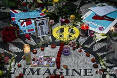 """Recuerdos y flores dejadas por fanáticos alrededor del mosaico """"Imagine"""" en la sección Strawberry Fields de Central Park en el 33th aniversario de la muerte del ex Beatle John Lennon, en Nueva York, 8 de diciembre de 2013. Mark David Chapman, el hombre que asesinó a John Lennon en la ciudad de Nueva York hace casi 36 años, se mantendrá en una prisión de alta seguridad después de que su pedido de libertad condicional fuera rechazado por novena vez desde el año 2000, dijeron funcionarios el lunes. REUTERS/Eduardo Munoz"""