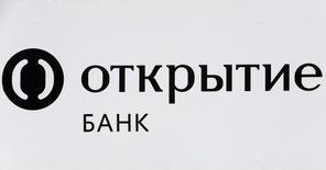 Логотип Банка Открытие на рекламном плакате в Москве. 13 июля 2016 года. Группа Открытие сократила объем задолженности по соглашениям репо с Центральным банком до 927,5 миллиарда рублей на 30 июня 2016 года с 1.265,4 миллиарда на конец 2015 года, говорится в отчете холдинга по международным стандартам. REUTERS/Sergei Karpukhin