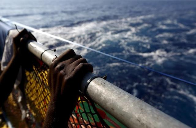 A migrant holds onto a railing at the stern of the Medecins Sans Frontiere (MSF) rescue ship Bourbon Argos somewhere between Libya and Sicily August 8, 2015.   REUTERS/Darrin Zammit Lupi