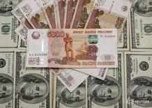Рублевые и долларовые купюры в Сараево 9 марта 2015 года. Рубль в небольшом плюсе утром четверга, реагируя на восстановление нефтяных котировок с двухнедельных минимумов при остановившем на мировых рынках рост долларе США. REUTERS/Dado Ruvic
