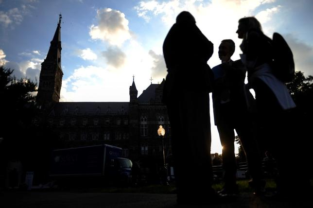 A group of people talk near the entrance to the Georgetown University campus, beneath the spire of Healy Tower in Washington June 14, 2012.  REUTERS/Jonathan Ernst