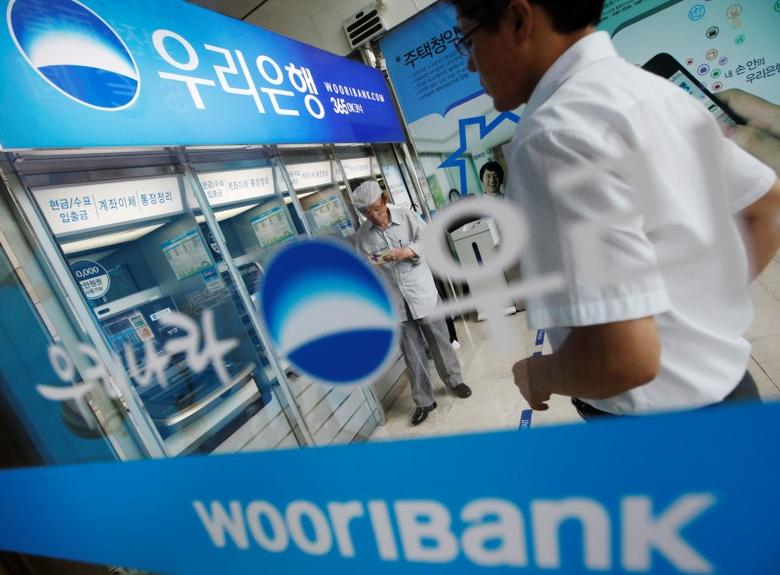People use automated teller machines at a branch of Woori Bank in Seoul July 18, 2012. REUTERS/Lee Jae-Won