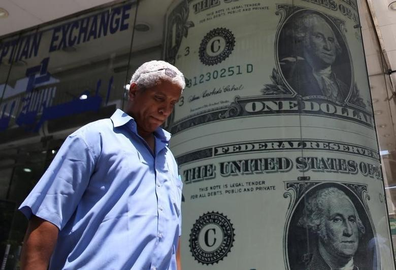 A man walks past a currency exchange bureau advertisement showing images of the U.S dollar and other currencies in Cairo, Egypt August 3, 2016. REUTERS/Mohamed Abd El Ghany