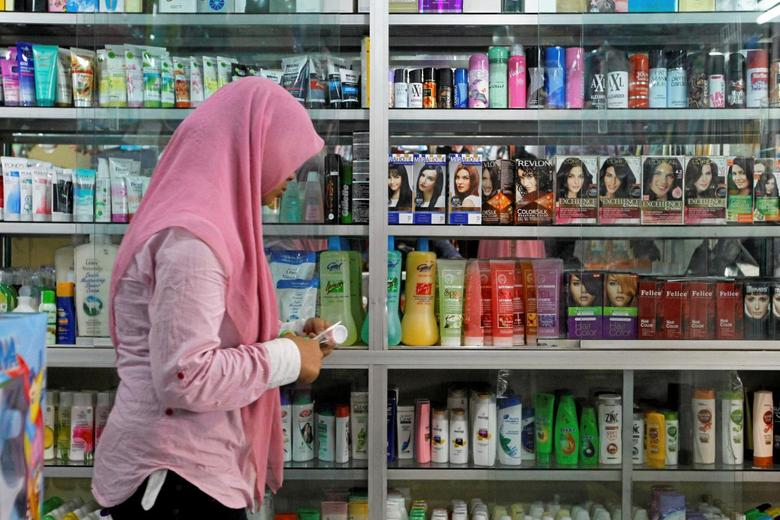 A saleswoman at a shop selling beauty products walks past a display cabinet while waiting for customers in a traditional market in Jakarta, Indonesia, August 25, 2016. Picture taken August 25, 2016. REUTERS/Iqro Rinaldi