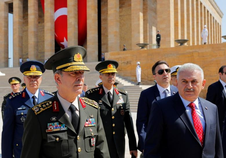 Turkey's Prime Minister Binali Yildirim (R), flanked by Chief of Staff General Hulusi Akar (L) and the country's top generals, leaves Anitkabir, the mausoleum of modern Turkey founder Mustafa Kemal Ataturk, after a wreath-laying ceremony ahead of a High Military Council meeting in Ankara, Turkey, July 28, 2016. REUTERS/Umit Bektas