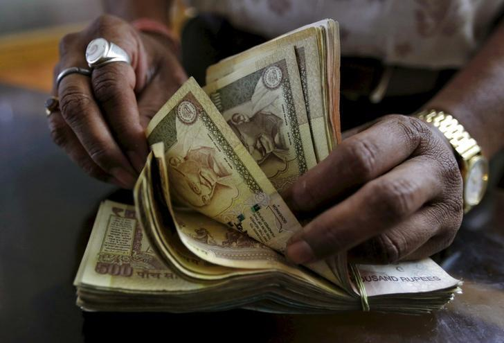 A money lender counts Indian rupee currency notes at his shop in Ahmedabad, India, May 6, 2015. REUTERS/Amit Dave/File Photo