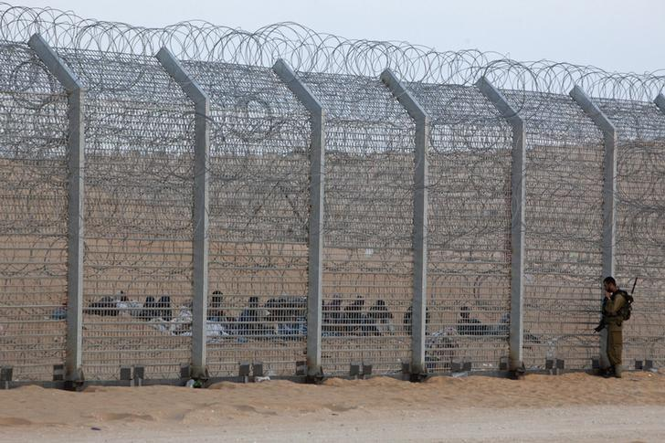An Israeli soldier stands near the border fence between Israel and Egypt as African would-be immigrants sit on the other side near the Israeli village of Be'er Milcha September 6, 2012. REUTERS/ Nir Elias/Files