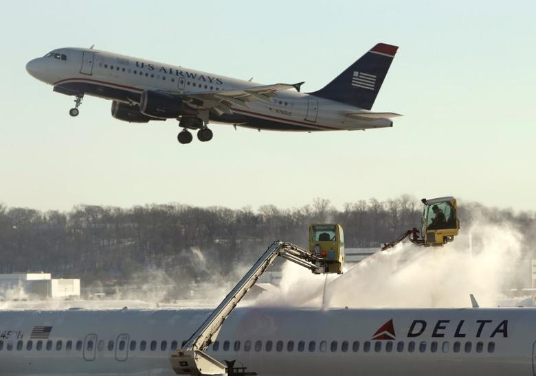 A Delta jetliner (bottom) is de-iced while a US Airways jet takes off at Reagan National Airport in Washington January 3, 2014. REUTERS/Gary Cameron
