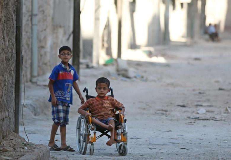 Boys, one of them in a wheelchair, go down a street in the rebel-held al-Sheikh Said neighbourhood of Aleppo, Syria September 1, 2016. REUTERS/Abdalrhman Ismail