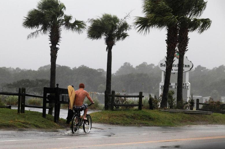 A surfer rides his bike down Atlantic Boulevard during the heavy rains of Tropical Storm Hermine as it passed through Garden City Beach, South Carolina. REUTERS/Randall Hill